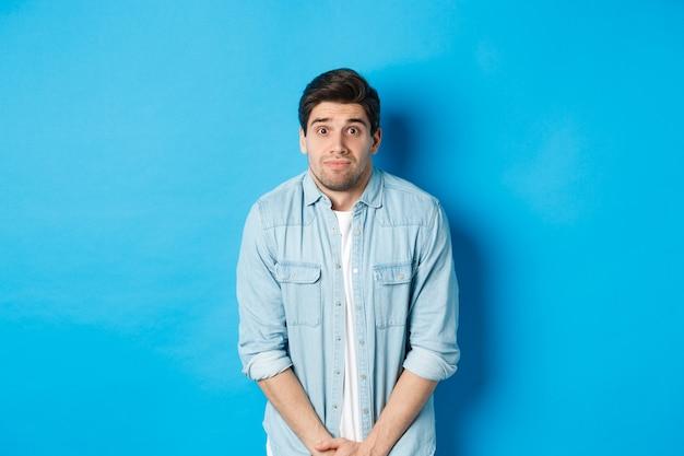 Beschaamde man wil plassen, wachtend in de rij voor toilet, staande tegen een blauwe achtergrond.