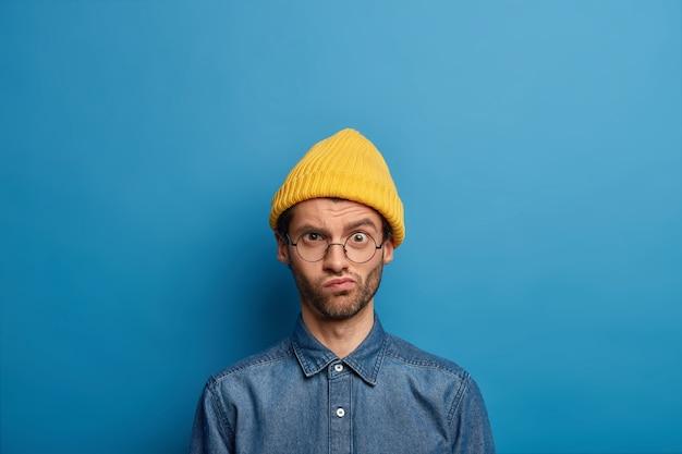 Beschaamde ongeschoren man kijkt met fronsende ontevreden gezichtsuitdrukking naar de camera, draagt een optische bril, een gele hoed en een spijkerblouse