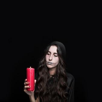 Beschaamde vrouw die brandende kaars bekijkt