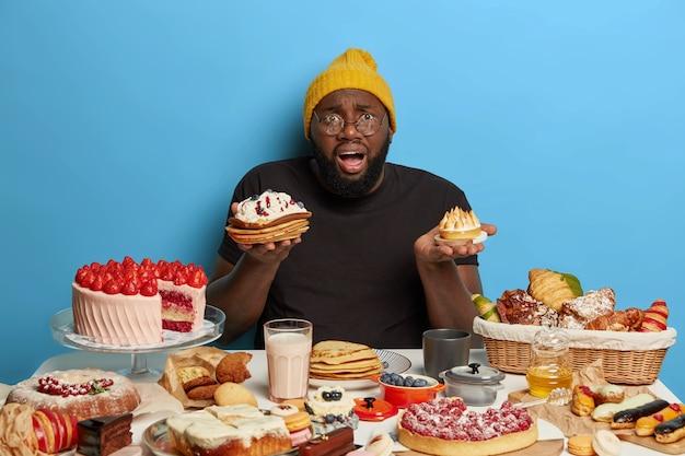 Beschaamde zwarte dikke bebaarde man houdt twee smakelijke taarten vast, kan niet kiezen wat hij wil eten, heeft een lekker zoet ontbijt, gekleed in vrijetijdskleding, geïsoleerd op een blauwe muur.