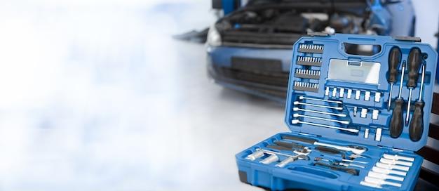 Beschadigde auto die moet worden gerepareerd en gereedschap close-up reparatie van transport bij een autoservice