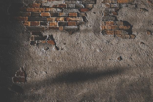 Beschadigde cementmuur met bakstenen