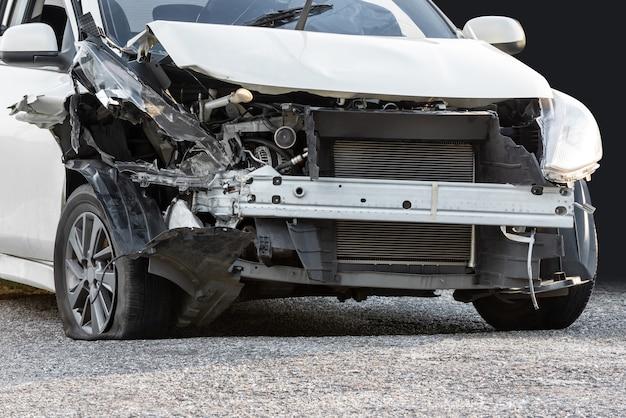 Beschadigde crash auto van ongeval en grond geïsoleerd op zwarte achtergrond met uitknippad