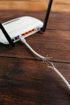 Beschadigde lan-kabel aangesloten op een router op een donkere houten tafel