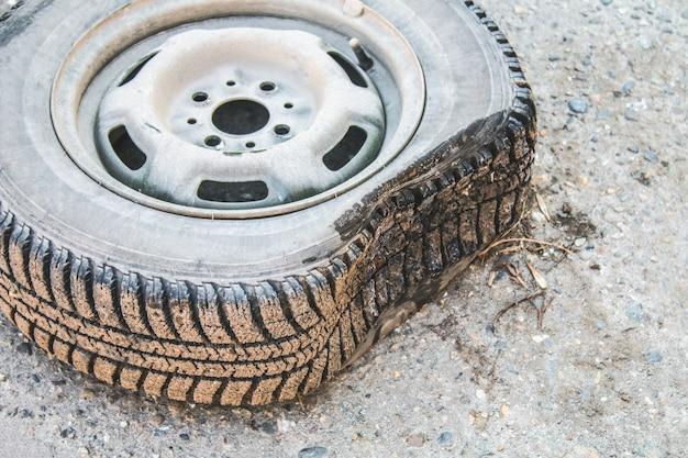 Beschadigde lekke band van een oude auto op de weg met selectieve nadruk.