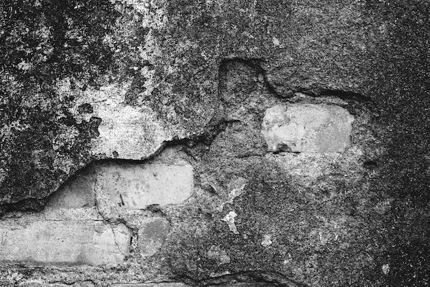 Beschadigde oude grungemuur met bakstenen die door tonen.