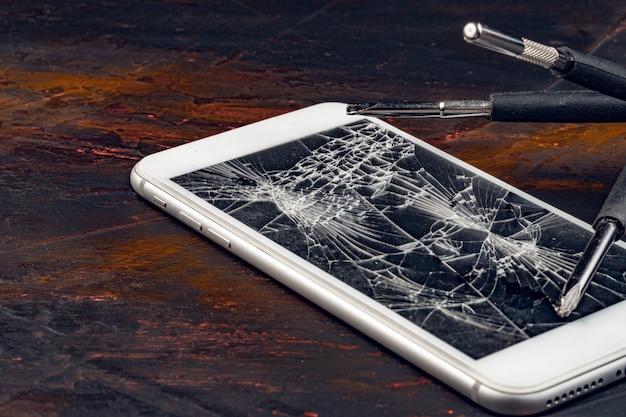 Beschadigde weergave van smartphone en tools
