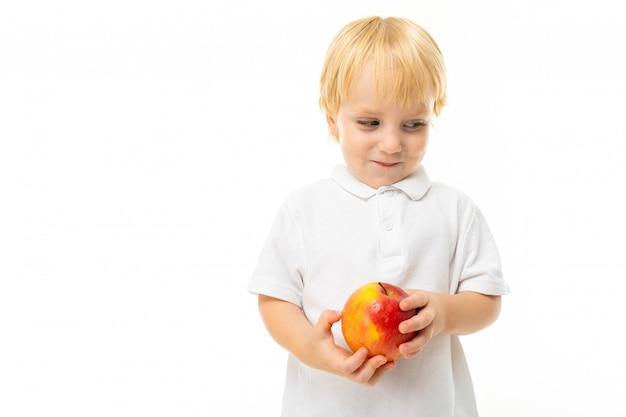 Bescheiden charmante blonde kind gekleed in een wit t-shirt met een appel in zijn hand op een witte muur met kopie ruimte