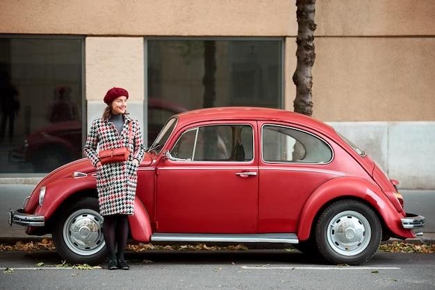 Bescheiden meisje staat glimlachend in de buurt van een rode retro auto en kijkt in de verte