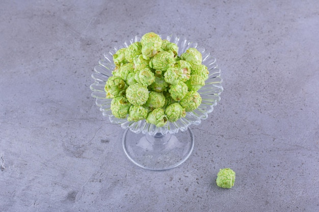 Bescheiden portie gearomatiseerde groene popcorn op een glazen snoephouder op marmeren achtergrond. hoge kwaliteit foto