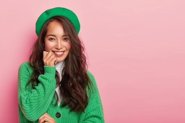 Bescheiden schattige jonge vrouw glimlacht zachtjes naar de camera, houdt de hand onder de kin, gekleed in modieuze groene outfit