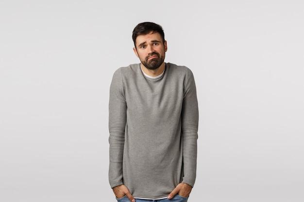 Bescheiden, zelfverzekerde jongeman die zich loser, gefrustreerd en verdrietig voelt terwijl hij in een grijze trui staat, zijn handen ophaalt in zijn handen, grijnst en gefronst fronsend, besluiteloos