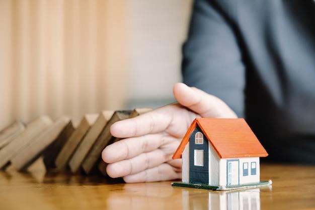 Bescherm het huis tegen omvallen van de houten blokken, verzekering en risico concept.