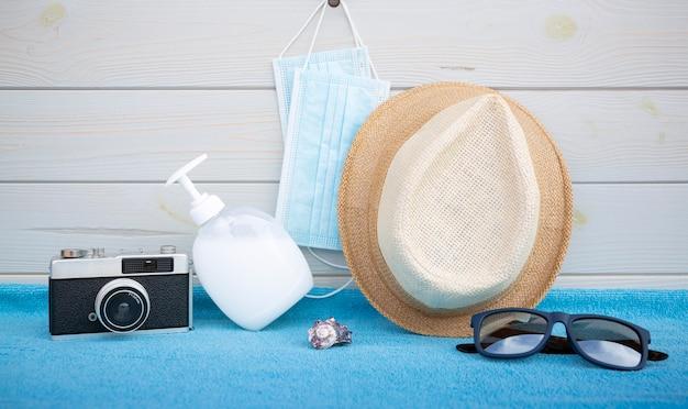 Beschermend gezichtsmasker, handgel, strohoed en fotocamera op blauwe handdoek en houten tafel.
