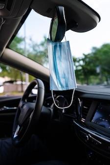 Beschermend gezichtsmasker hangend aan de achteruitkijkspiegel van een auto