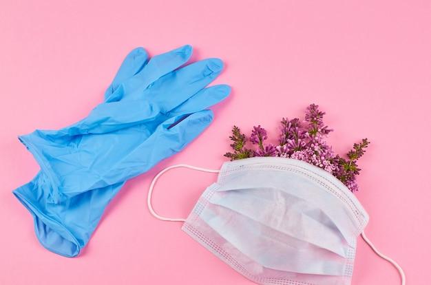 Beschermend gezichtsmasker met bloemen en blauwe nitril handschoenen.