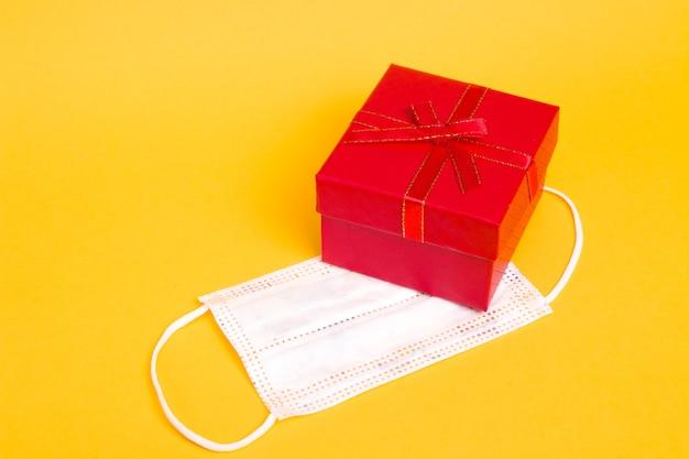 Beschermend masker en rode geschenkdoos op gele achtergrond kopie ruimte