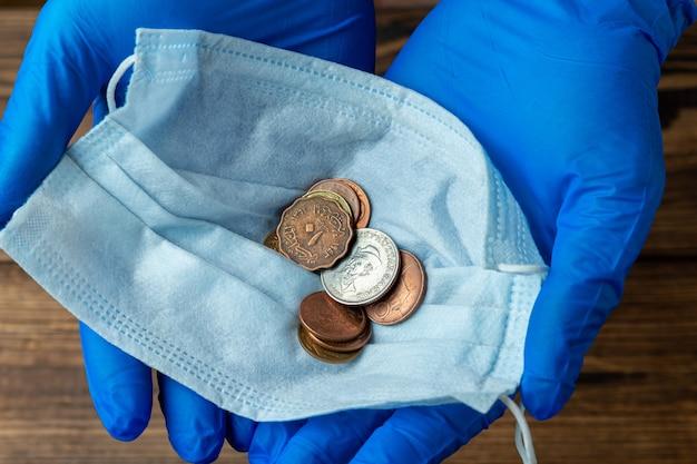 Beschermend masker met munten in handen met medische handschoenen