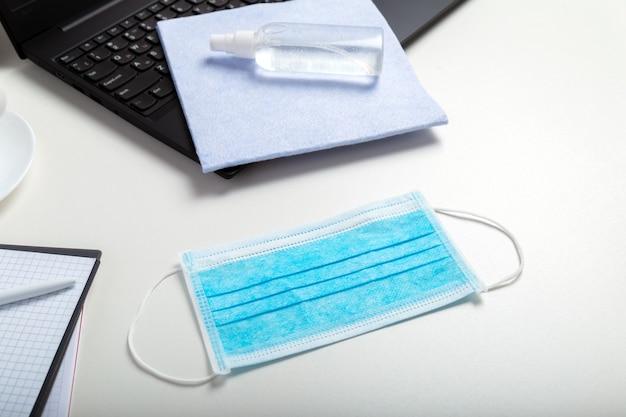Beschermend medisch blauw masker, desinfecterende spray. alcoholdesinfecterend middel op office werkplek, laptop op witte tafel. nieuwe normale normen voor thuishygiëne op kantoor tijdens coronavirus covid 19.