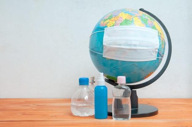 Beschermend medisch gezichtsmasker en effectieve alcoholoplossing ter voorkoming van open oppervlakken op de wereldbol