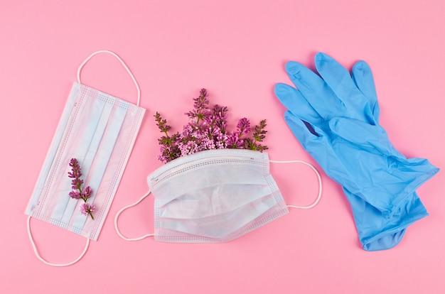 Beschermende gezichtsmaskers met bloemen en blauwe nitrilhandschoenen