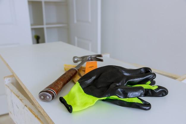 Beschermende handschoenen met een hamer ambachtelijke bouwer apparatuur