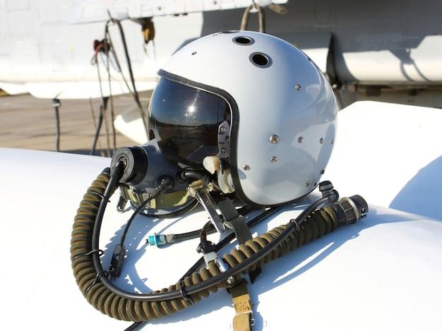 Beschermende helm van de piloot tegen het vliegtuig met een zuurstofmasker op een brandstoftank