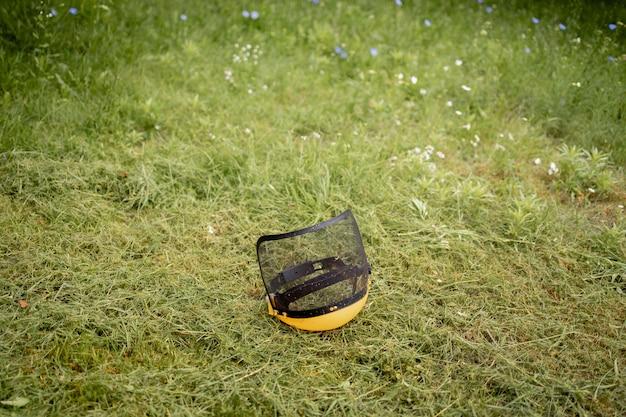 Beschermende helm voor de maaier op gemaaid gras.