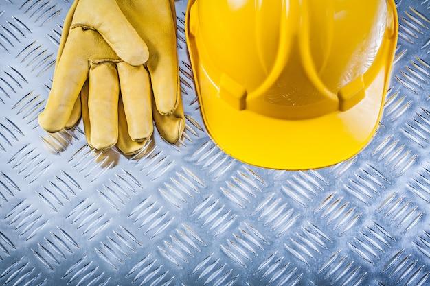 Beschermende lederen handschoenen bouwvakker op gegroefde metalen plaat bouwconcept