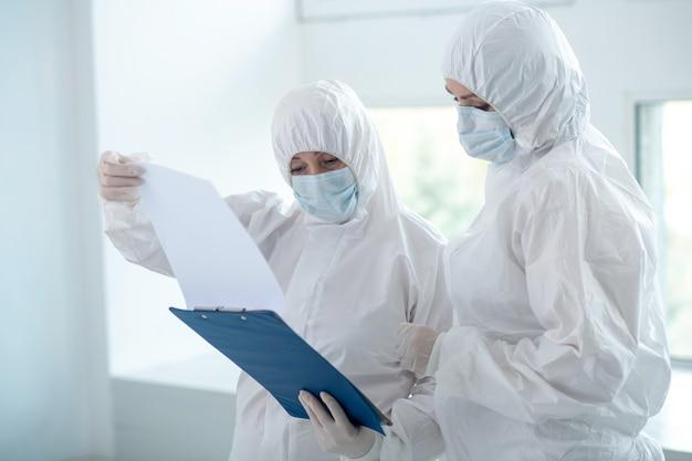 Beschermende maatregelen. gezondheidswerkers in beschermende kleding en medische maskers kijken door documenten op clip map