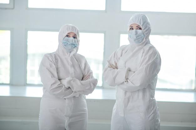 Beschermende maatregelen. gezondheidswerkers in beschermende kleding en medische maskers staan met hun armen over elkaar