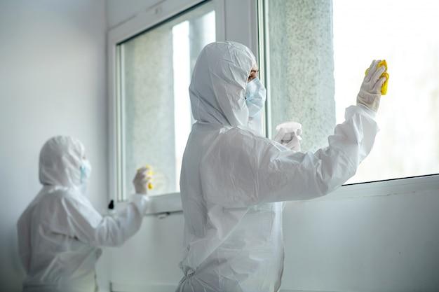 Beschermende maatregelen. gezondheidswerkers in beschermende kleding en medische maskers venster desinfecteren