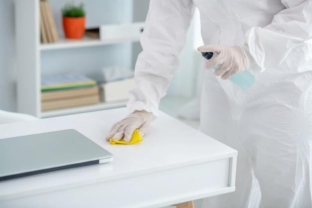 Beschermende maatregelen. het close-up van medische arbeider dient handschoenen in die desinfecterend middel op lijst bespuiten