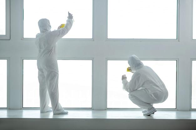 Beschermende maatregelen. medisch personeel in beschermende kleding en medische maskers die ruiten schoonmaken en desinfecteren