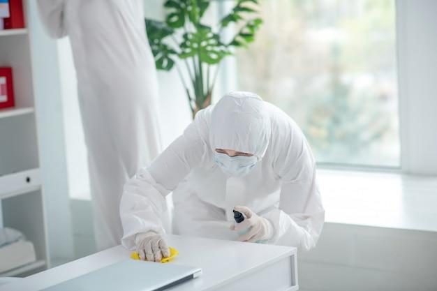 Beschermende maatregelen. medisch-werker in beschermende kleding en medische masker desinfecterende tafel, een andere werknemer achter staan