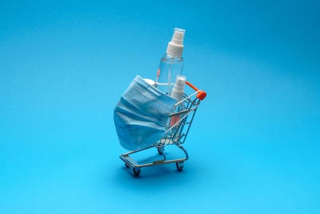 Beschermende maskers en antibacteriële desinfecterende ontsmettingsgel in een klein winkelwagentje op blauwe achtergrond met kopie ruimte.