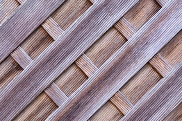 Beschermende muur van houten piketomheining met een gegroefd oppervlak.