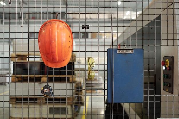 Beschermende staven met helm, bril, klembord en handgereedschap die eraan hangen in de werkplaats van een industriële fabriek