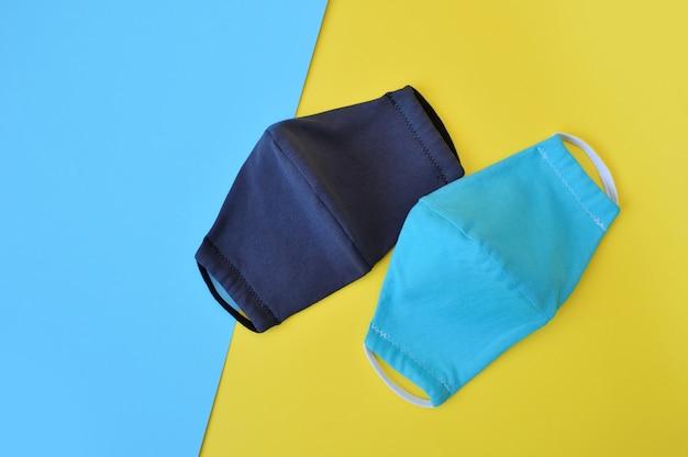 Beschermende twee turquoise en donkergrijze gezichtsmaskers op blauwe en gele achtergrond. coronavirus bescherming
