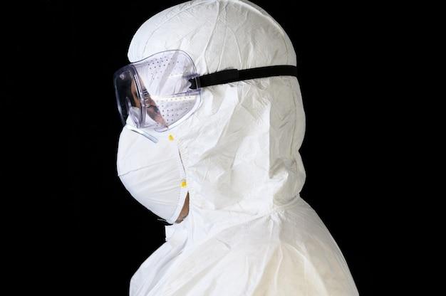 Beschermende uitrusting covid-19. zijaanzichtportret van arts of verpleger die persoonlijke beschermingsmiddelen op geïsoleerde zwarte dragen