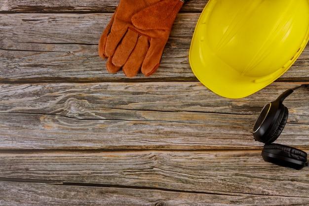 Beschermende werkkleding veiligheidsnorm constructie veiligheid oorbeschermers lederen veiligheidshelm beschermende handschoenen op houten