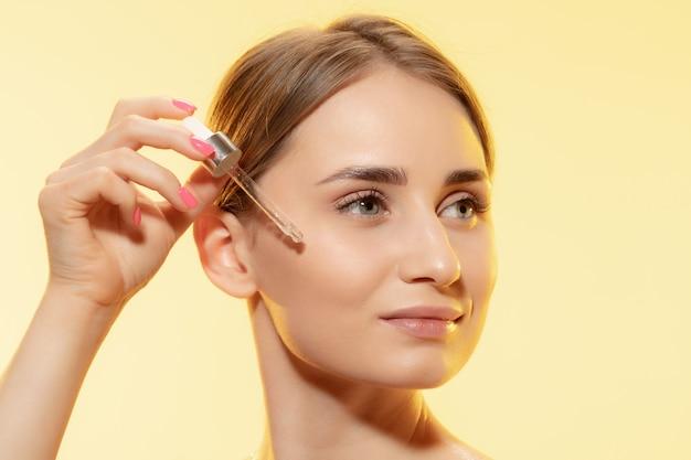 Bescherming. close up van mooi vrouwelijk gezicht met het gieten van etherische olie