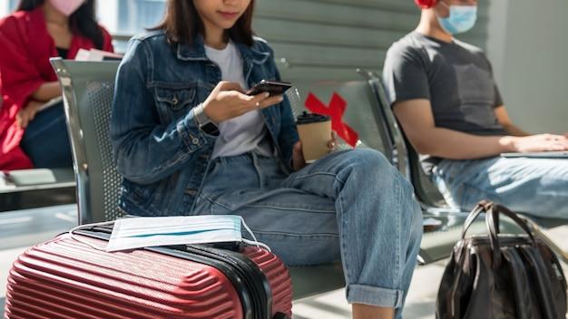 Bescherming gezichtsmasker op bagage terwijl toeristische meisje koffie drinkt en teksten op smartphone in de wachtruimte