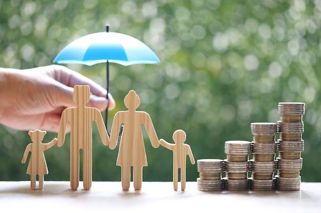 Bescherming, modelfamilie met hand die de paraplu en stapel muntgeld op natuurlijke groene achtergrond houdt, financiële verzekering en veilig investeringsconcept investment