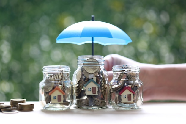 Bescherming, modelhuis en gouden muntgeld in de glazen fles met hand die de paraplu op natuurlijke groene achtergrond houdt, financiële verzekering en veilig investeringsconcept