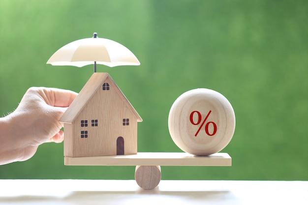 Bescherming, modelhuis met hand die de paraplu en het percentagesymboolpictogram op de houten schaalwip op natuurlijke groene achtergrond houdt, de financiële verzekering en het veilige investeringsconcept