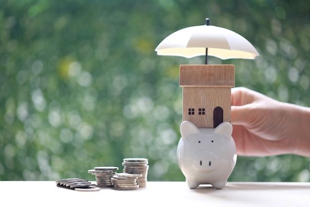 Bescherming, modelhuis op spaarvarken met hand die de paraplu en stapel muntgeld op natuurlijke groene achtergrond houdt, financiënverzekering en veilig investeringsconcept