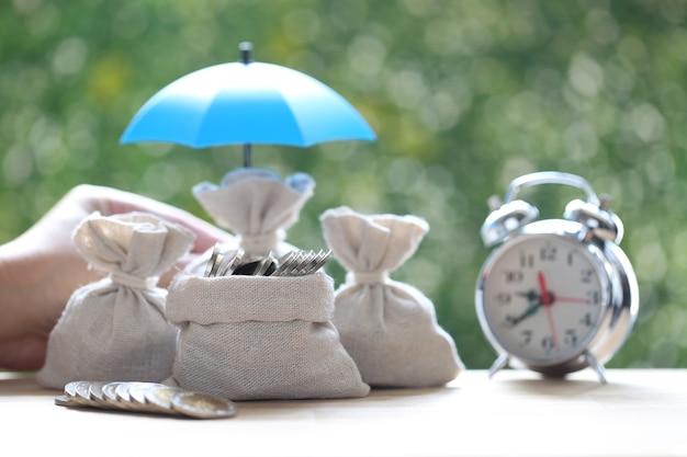Bescherming, muntengeld in de zak onder de paraplu op natuurlijke groene achtergrond, financiële verzekering en veilig investeringsconcept