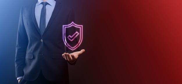 Bescherming netwerk beveiligingscomputer in de handen van een zakenman. zaken, technologie, cyberveiligheid en internetconcept - zakenman die op schildknop drukt op virtuele schermen gegevensbescherming.