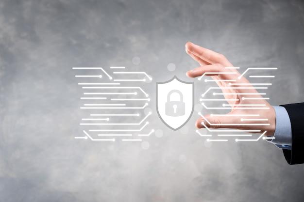 Bescherming netwerkbeveiligingscomputer en veilig uw gegevensconcept, zakenman houden schild beschermen pictogram. slotsymbool, concept over veiligheid, cyberveiligheid en bescherming tegen gevaren.